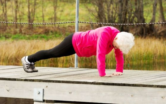 Active grandmum doing push-ups on fresh air.